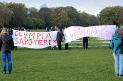 GegnerInnen der Hamburger Olympiabewerbung protestieren im Hamburger Stadtpark  mit einem Transparent: Olympia sabotieren / Olympia verhindern.