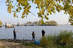 Angler auf Entenwerder in Hamburg Rothenburgsort am Ufer der Norderelbe - im Hintergrund das Sturmflut Sperrwerk Billwerder Bucht.