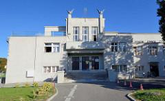 SOKOL Gebäude in Terezin; Sozialistische Architektur - Falken, Greifvögel mit aufgestellten Schwingen auf dem Dach.