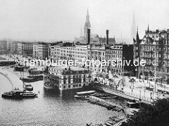Historische Luftaufnahme vom Hamburger Jungfernstieg - Bootsverleih mit Ruderbooten beim Alsterpavillion - Alsterdampfer am Anleger; Rathausturm und Kirchturm der St. Nikolaikirche.
