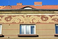 Wohngebäude in Terezin / Theresienstadt - Fries unter dem Dach, Mutter mit Kind auf dem Arm.