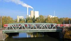 Blick von der Tiefstacker Brücke auf den Tiefstackkanal; ein S-Bahnzug überquert die Eisenbahnbrücke - Rauch steigt aus einem Schornstein der Müllverwertungsanlage MVA Borsigstrasse in Hamburg Billbrook.