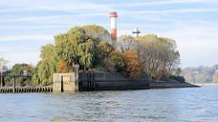 Einfahrt zum Petroleumhafen Hamburg -  hohe Bäume. Der Petroleumhafen soll im Rahmen der Hamburger Hafen-Westerweiterung zugeschüttet und als Container-Terminal genutzt werden. Hinter den Bäumen der Leuchtturm Oberfeuer Bubendey-Ufer - der Turm ist r
