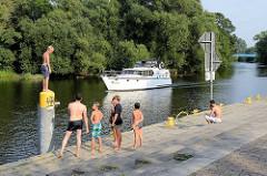 Sportboot auf der Havel in Oranienburg - Kinder / Jugendliche am Flussufer - Anleger.