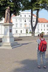 Blick auf das Schloss Oranienburg - eine Touristin fotografiert das Louise-Henriette-Denkmal von Wilhelm Wolff (1858).