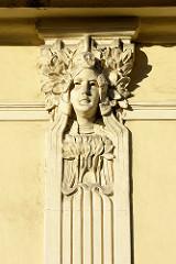 Jugenstildekor - Frauengesicht mit Blumen / Blüten, floralen Elementen - Stuck einer Hausfassade in Terezin, Theresienstadt.