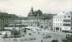Historische Ansicht vom Karlsplatz / Karlovo náměstí in Kolin -  städtische Architektur des späten Barock, Renaissance und klassizistischer Historismus. Marktstände sind abgeräumt - der Marktplatz wird mit einem Reisigbesen gefegt; Fassadenschild