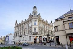 Gründerzeitgebäude mit Uhrenturm und Fassadenmalerei, Figuren / Eckgebäude - andere Strassenseite Architektur der 1920er Jahre, Putzfassade.
