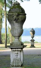Deckelvase / Ziervase aus Stein - antike Form mit Maskaron; Dekoration im Rheinsberger Schlossgarten. Im Hintergrund der Grienericksee.