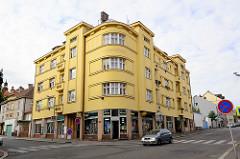 Architektur der 1920er Jahre - Eckwohnhaus / runde Ecke mit gelber Fassade in Kolin