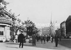 Altes Bild vom Fussweg vor dem Alsterpavillon am Jungfernstieg, Palmen stehen vor dem Restaurant - im HIntergrund das Gebäude vom Haus Vaterland und der Kirchturm der Hamburger St. Petri-Kirche.