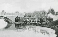 Miniaturbahn mit Fahrgästen, Lokomotive mit Dampf aus dem Schornstein - Gelände Hagenbecks Tierpark in Hamburg Stellingen.