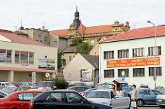 Parkplatz mit Autos vor Geschäften - im Hintergrund das Koliner Schloss mit Kupferturm.