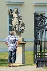 Eingang zum Schloss Rheinsberg, Eisentor - Tourist betrachtet Skulptur.