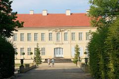 Seitenansicht vom Schloss Rheinsberg - Brücke mit Amphoren, Touristen im Schlossgarten.