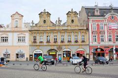Karlsplatz / Karlovo náměstí in Kolin - städtische Architektur des späten Barock, Renaissance und klassizistischer Historismus. Barockgebäude mit Geschäften, parkende Autos - FahrradfahrerIn.