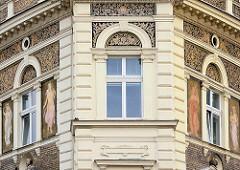 Prunkvolles mehrstöckiges Wohnhaus mit ganzflächig dekorierter / bemalter Fassade - weibliche Figuren, Büsten.