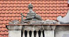 Dachdekor - Skulptur, Sphinx mit abgefallenem Flügel; Architektur in Kolin.