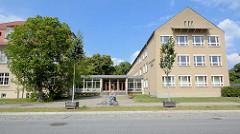 Heinrich Rau Schule Rheinsberg - graue Putzfassade.