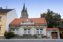 Altes Gebäude - Baustil der Gründerzeit mit klassizistischem Stuckdekor; im Hintergrund die Türme vom Dom in Kolín, St. Bartholomäus Kirche.