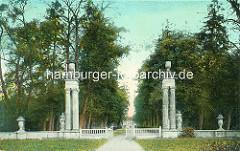 Historische Ansicht vom Eingang des Schlossparks in Rheinsberg. Kannelierte Säulen mit Vasendekor - Skulpturen und niedrige Steinmauer - im Hintergrund das Schloss Rheinsberg.