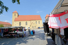 Evangelische Kirche St. Laurentius, Rheinsberg - Ursprungsbau aus dem 13. Jahrhundert. Die Fassade der Feldsteinkirche wurde Ende des 19. Jhd. verputzt. Wochenmarkt mit Kleidung auf dem Kirchenplatz.
