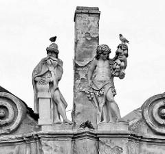 Skulpturen auf dem Dach eines historischen Hauses am Karlsplatz / Karlovo náměstí in Kolin - Tauben turteln oder sitzen auf den historischen Figuren, schiefer Schornstein.