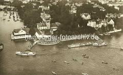 Historische Luftaufnahme vom Uhlenhorster Fährhaus an der Hamburger Aussenalster - die Terrasse des Cafés ist mit Gästen dicht besetzt,  Ruderboote schwimmen auf dem Wasser  - Alsterdampfer legen am Steg an. Im Hintergrund die Langenzugbrücke und