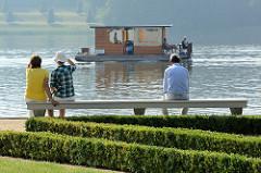 Touristen sitzen auf einer Steinbank im Schlossgarten vom Rheinsberger Schloss und blicken auf den Grienericksee, auf dem ein Hausboot fährt.