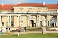Touristen im Schlossgarten vor dem Schloss Rheinsberg.
