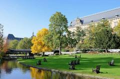 Wallanlagen / Planten un Blomen in Hamburg - Holzstühle auf der Wiese vor dem Strafjustiz - Gebäude am Sievekingplatz; Ginkobaum mit gelben Herbstlaub.