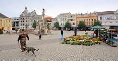 Karlsplatz / Karlovo náměstí in Kolin -  städtische Architektur des späten Barock, Renaissance und klassizistischer Historismus. Wochenmarkt mit Blumenstand - Spaziergänger in Tarnuniform mit Hund.