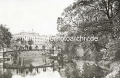 Historsiche Hamburger Wallanlagen beim Botanischen Garten - Brücke über den Wallgraben, Parkbesucher; im Hintergrund die Architektur der Oberzolldirektion.