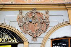Wappenrelief, nackte Frauen - Löwe stehend auf den Hinterbeinen mit Weltkugel in den Pfoten - Hausfassade in Kolin, Tschechische Republik.