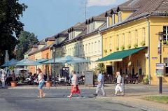 Historische einstöckige Wohnhäuser mit Mansardenfenstern - Restaurant im Erdgeschoss, Gäste sitzen an Tischen im Freien - Schlossplatz Rheinsberg.