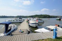 Marina / Sportboothafen in Rheinsberg - Grienericksee; Motorboote liegen am Steg.
