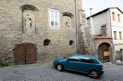 Historische religiöse Reliefs an der Fassade vom Dekanatsgebäude in Kolin - Auto im Parkverbot mit Parkkralle.