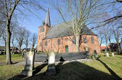 St. Andreaskirche in Lübeck Schlutup - ev. luth. Saalkirche der Backsteingotik, Friedhof und altes Fischerboot.
