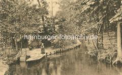 Blick in einen Fliess im Spreewald - ein Kind / Mädchen stakt eine Kahn - Wohnhäuser, Holzhütten am Ufer.