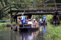 Kahnfahrt mit Touristen durch den Spreewald bei Lübbenau - Holzbrücken.
