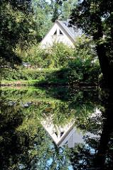 Modernes Wohnhaus am Wasser - der Giebel spiegelt sich im Wasser des Spreearms bei Lübben.