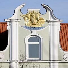 Fassadendekor - Gebäude an der Untertrave in Lübeck, goldene Kogge.