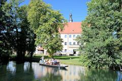 Spreewaldkahn mit Touristen auf einem Kanal in Lübben - Blick zum Schloss Lübben / Stadt- und Regionalmuseum.