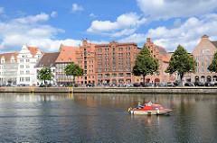 Blick über die Trave zu historischen Gebäuden an der Untertrave  - Backsteinspeicher; ein Sportboot fährt flussaufwärts.