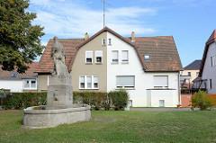 Wohnhaus / Doppelhaus mit unschiedlich gestrichener  Fassade, Brunnen - Trüschels Kolonie; Wohnanlage für Arbeiter - erbaut 1918  in  Lübben (Spreewald).
