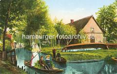 Altes Bild aus dem Spreewald - Holzkähne auf dem Wasser, Kinder auf der Sitzbank; Boote am Ufer im Gras - Wohnhaus mit Reetdach und Holzfassade.