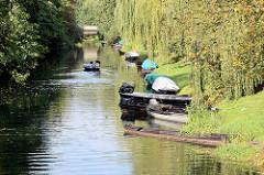 Kähne liegen am Ufer eines Spreearms in Lübben / Spreewald - ein Kahn fährt mit Motorantrieb auf dem Kanal.