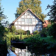 Fachwerkgebäude / Wohnhaus am Wasser, Spreekanal; Bootsanlegestelle mit Holzboot.