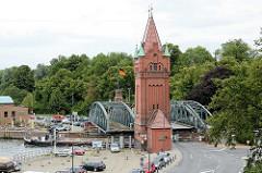 Angehobene Hubbrücke / Marstallbrücke, ein Binnenschiff fährt von der Kanal-Trave in die Stadt-Trave ein - im 25m hohen Brückenturm befinden sich die Hydraulikzylinder, die die Bewegung der Hubbrücke erzeugen.