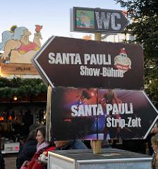 Weihnachtsmarkt Santa Pauli auf dem Spielbudenplatz in Hamburg St. Pauli; Hinweisschilder zur Show Bühne, WC und Strip Zelt.